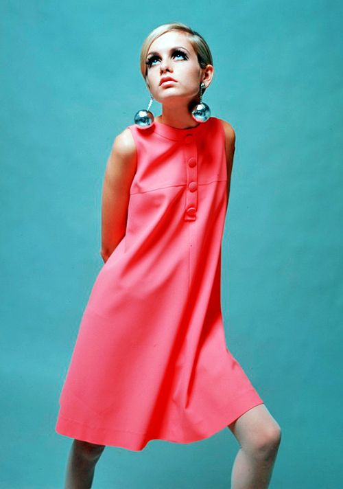 British model Twiggy poses for the camera in pink dress and iconic disco ball earrings