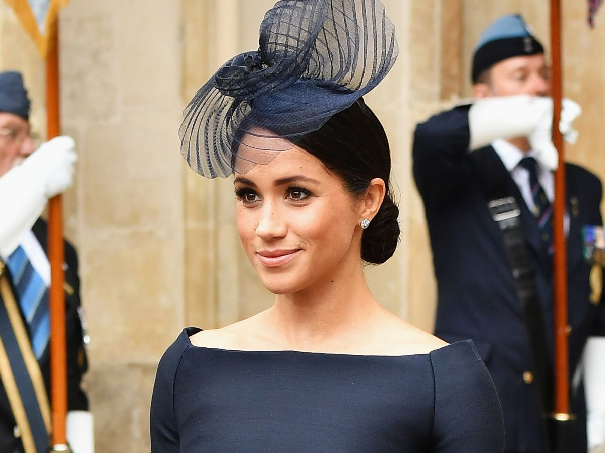 Meghan Markle wearing a navy dress with bateau neckline